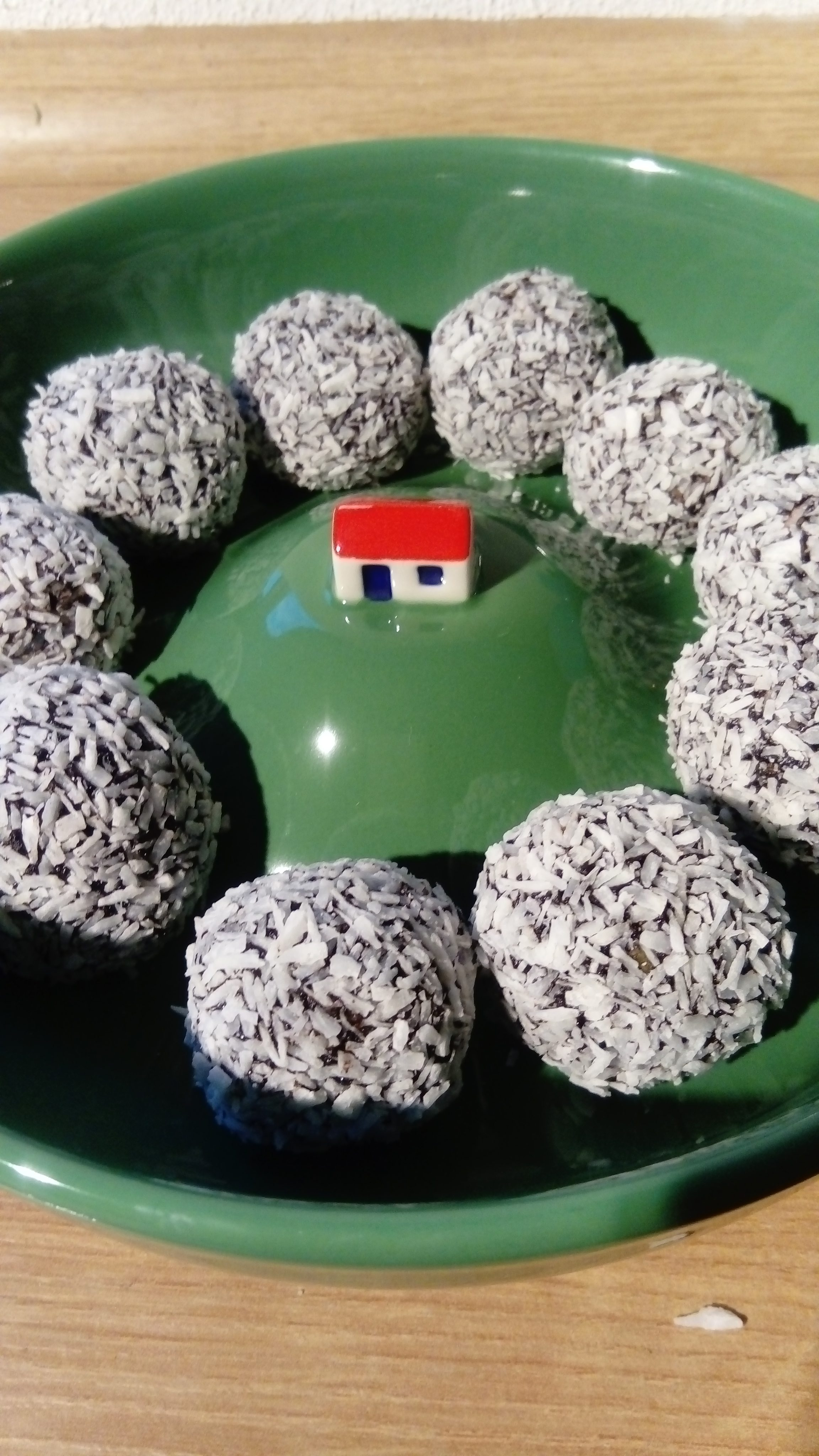 home-made bliss balls placed in a green porcelain dish with a small house in the middle