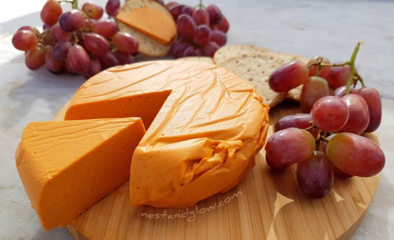 vegan smoked cheese served with red grapes on a wooden board